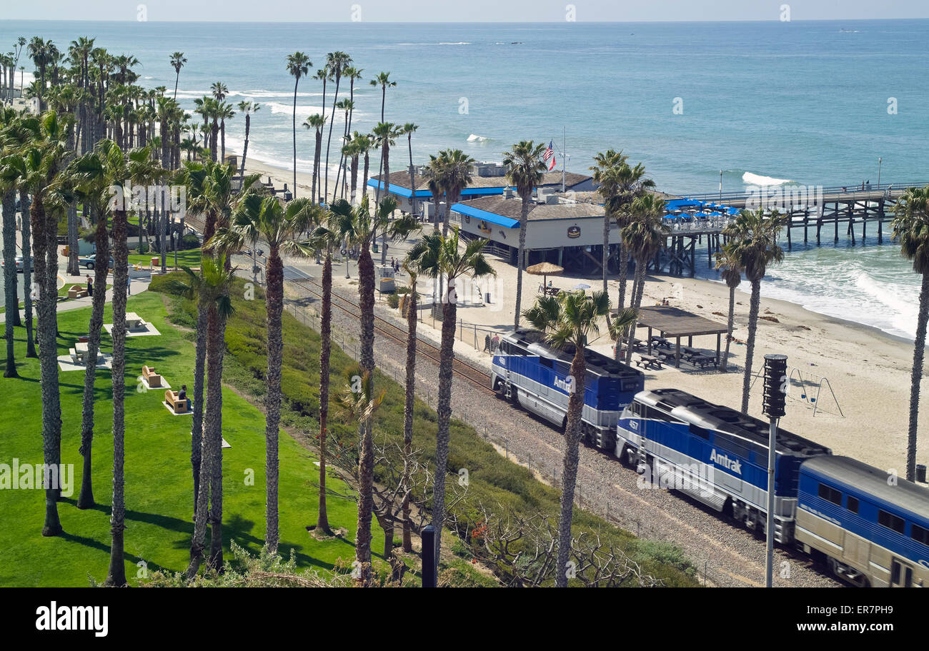 Passengers on an Amtrak train enjoy great views of the Pacific Ocean as they speed past the San Clemente pier in Stock Photo