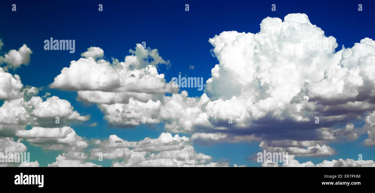 Puffy white cumulus clouds have been digitally enhanced to show against a sky of varied blue colors. - Stock Image