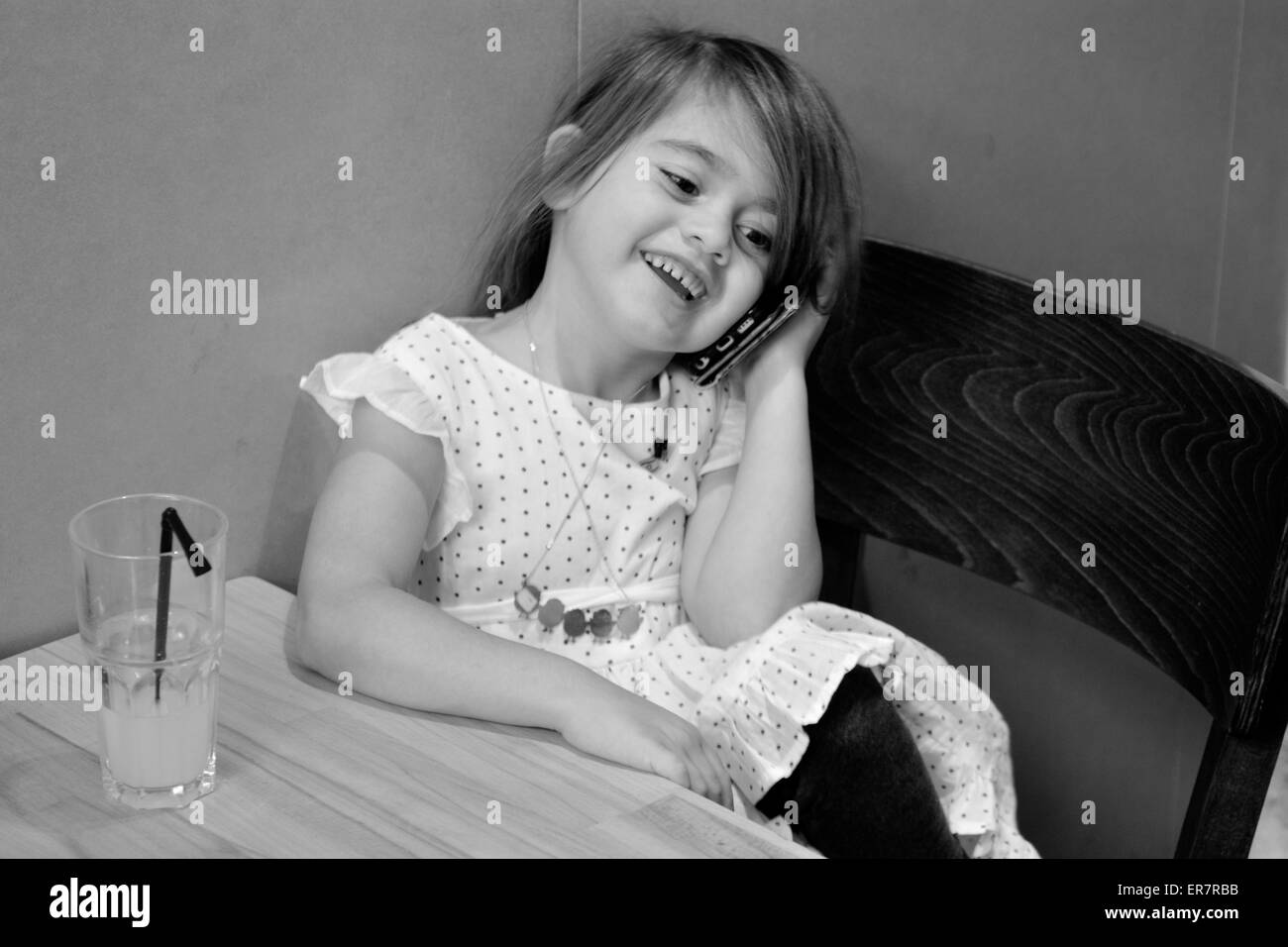 Little girl speak on the phone in a restaurant. Concept photo of long distance ,call ,communication, telephone, - Stock Image
