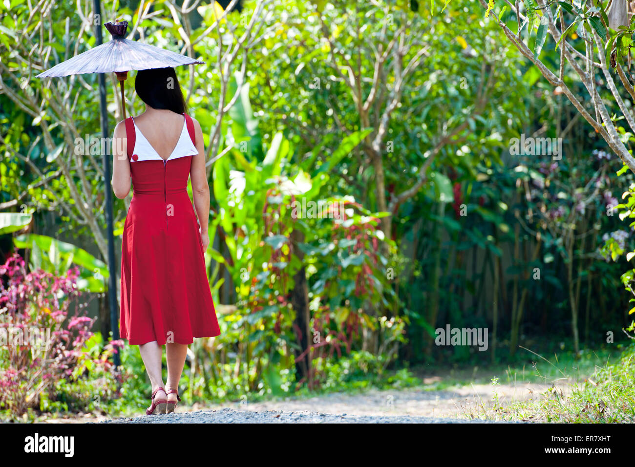 Beautiful Woman In Red Dress Walking Through A Thai Garden Stock