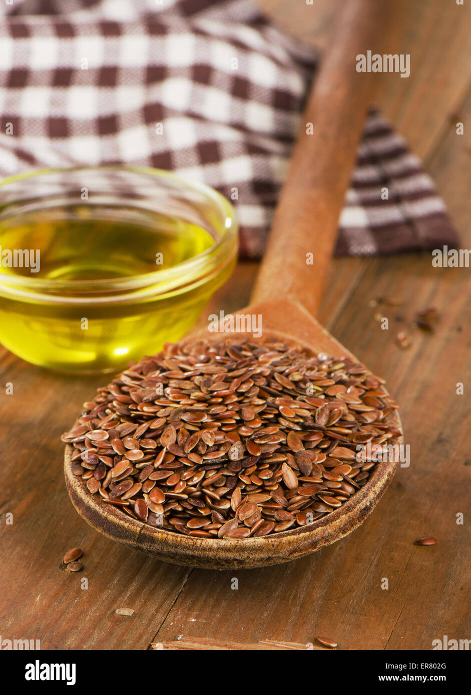 Brown Flax Seeds On Spoon And Flaxseed Oil On Wooden Table Stock