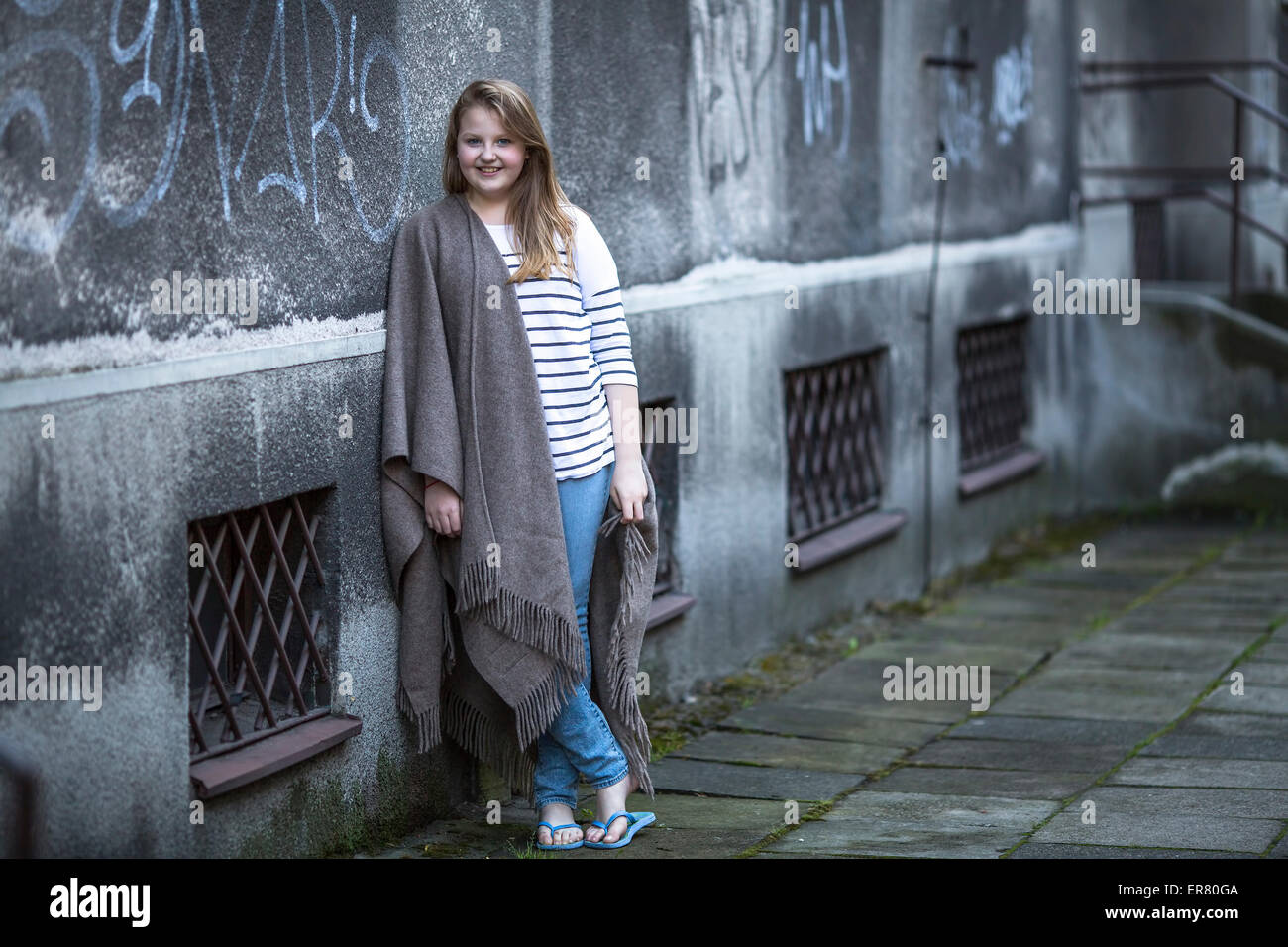 Teenage girl in poncho in the street near the house at evening. - Stock Image