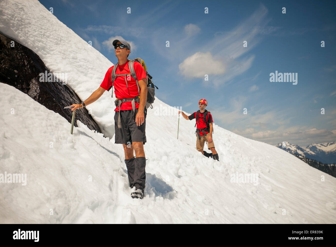 Two climber cross a snowfield high in the mountains. - Stock Image