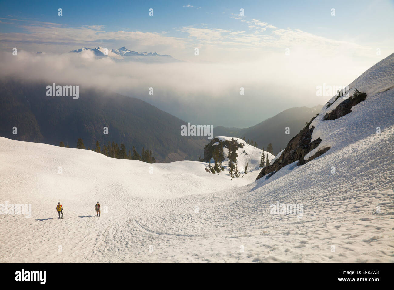 Two climbers descend a snowfield after a trip into the mountains. - Stock Image