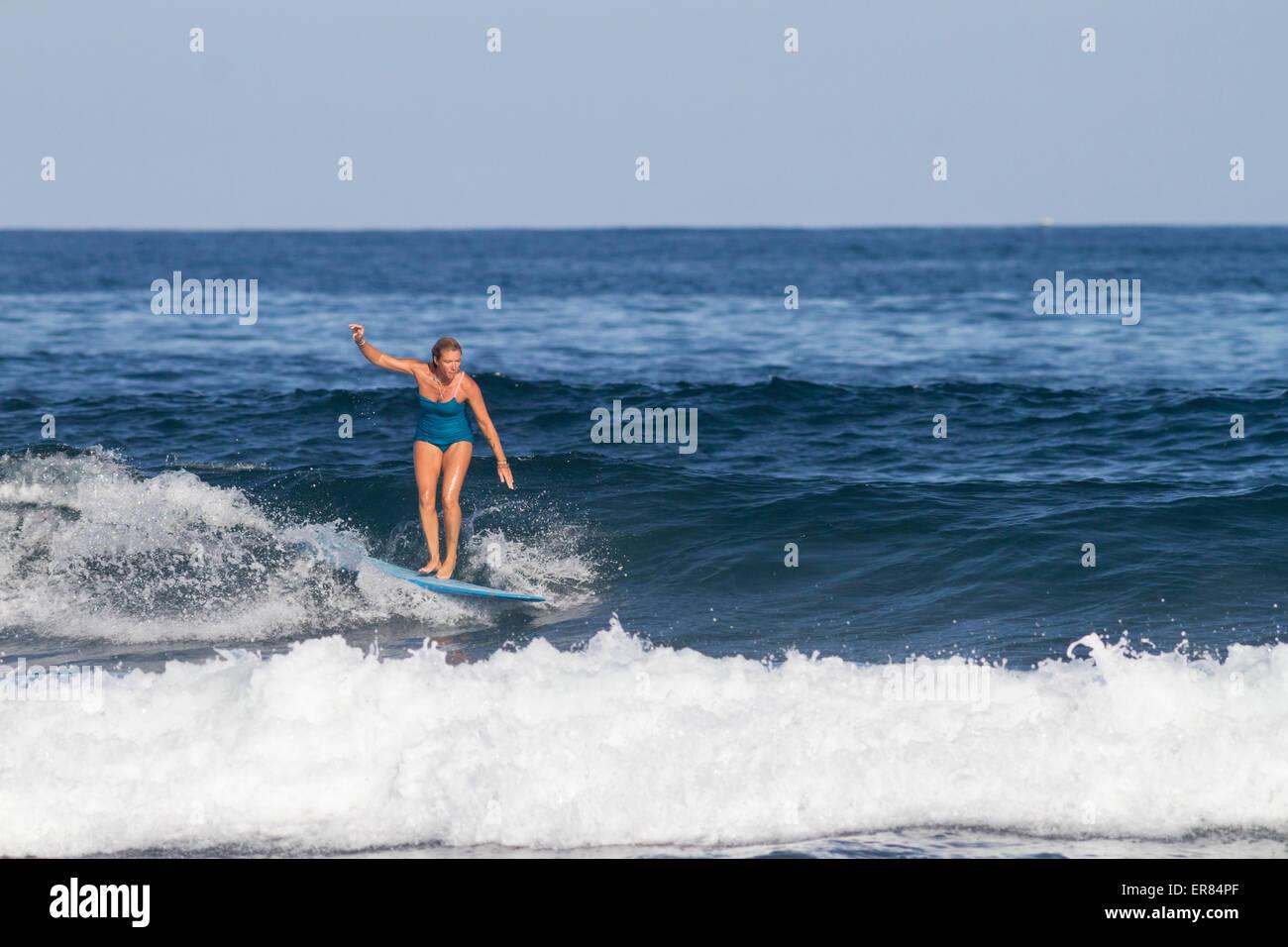 Blonde surfer girl surfing in bikini with a longboard - Stock Image