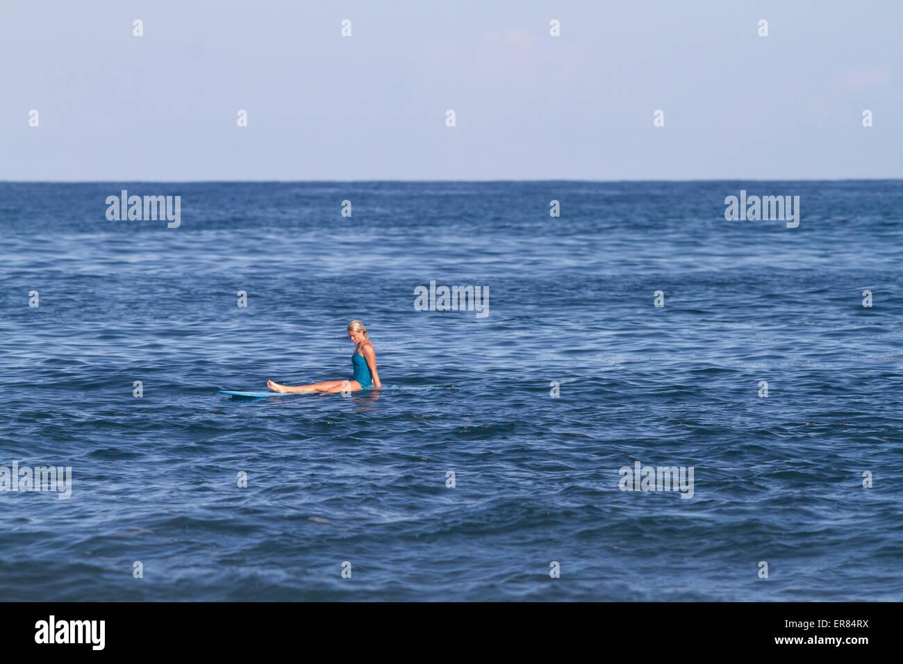 Blonde surfer girl surfing in classic swimwear bikini sitting on a longboard - Stock Image