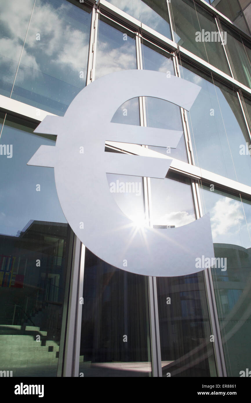 Low angle view of euro symbol outside office building - Stock Image
