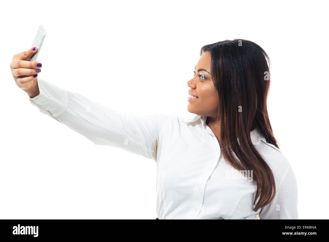 Happy afro american businesswoman making selfie photo on smartphone isolated on a white background - Stock Image