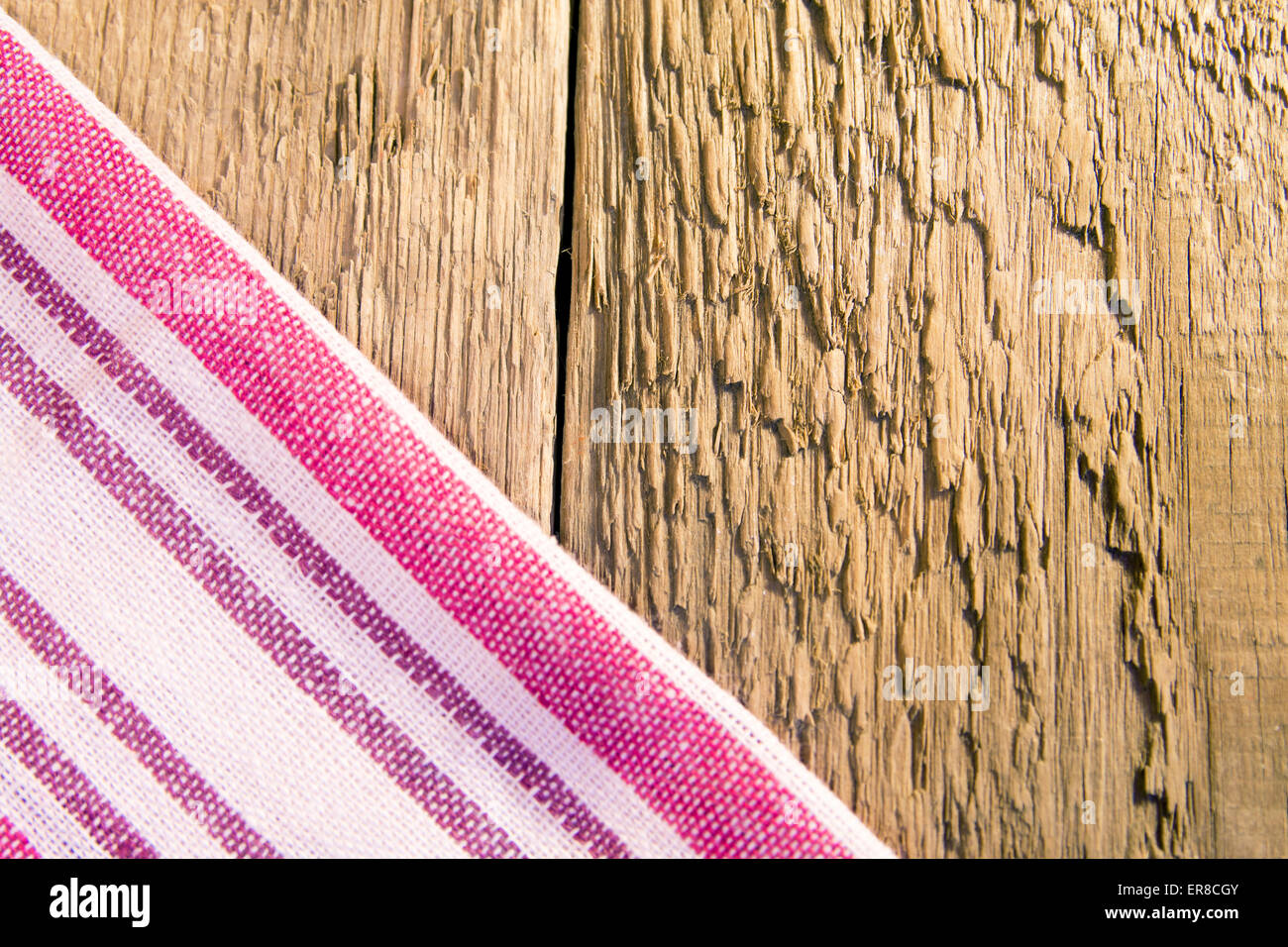 striped napkin on rustic wooden backround (table, texture) - Stock Image