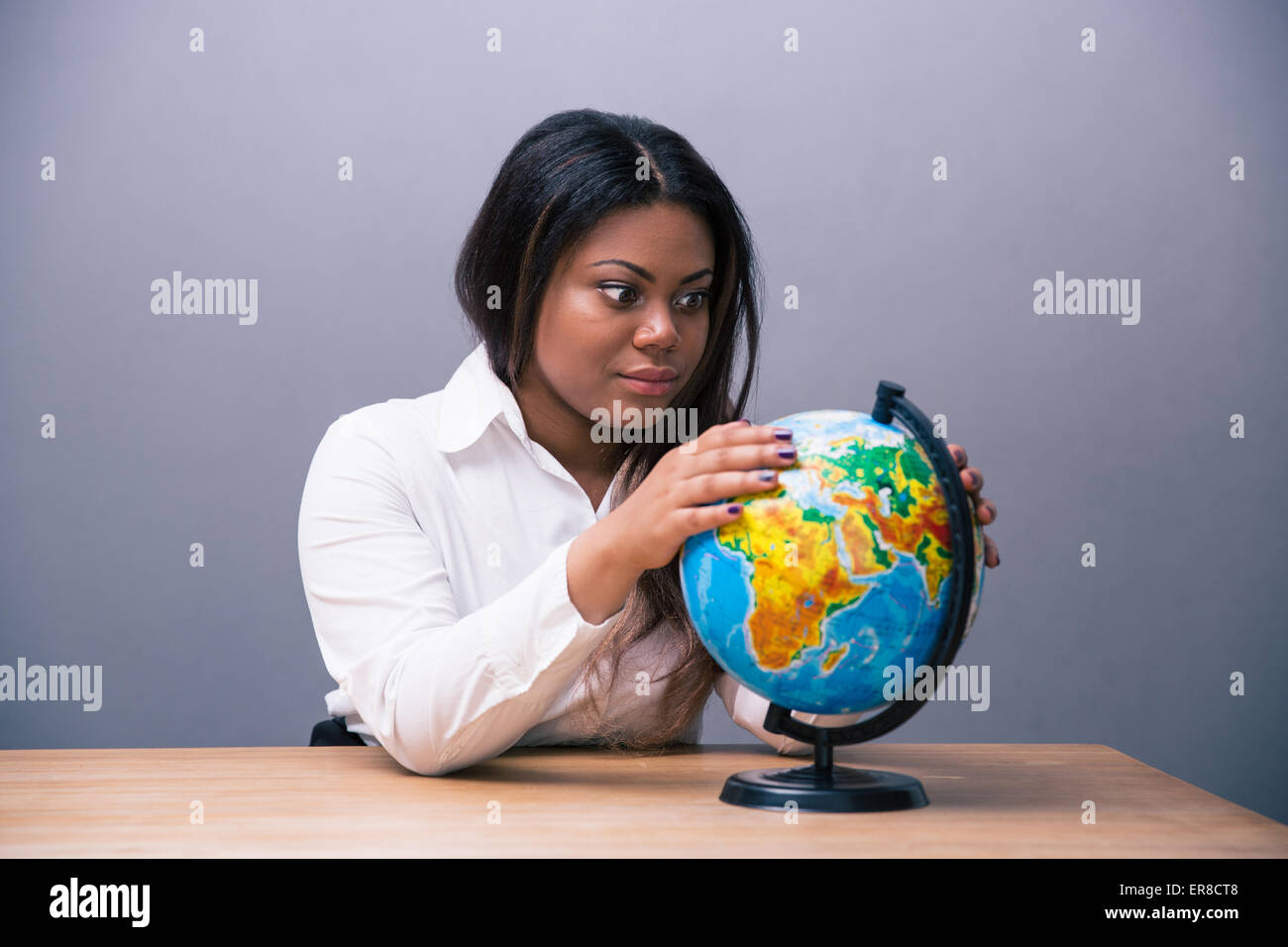 African businesswoman sitting at the table with globe over gray background - Stock Image