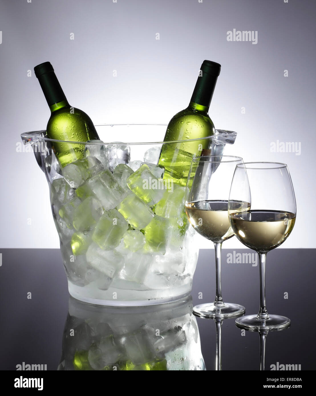 Two glasses of fresh white wine next to a cooler with ice. - Stock Image
