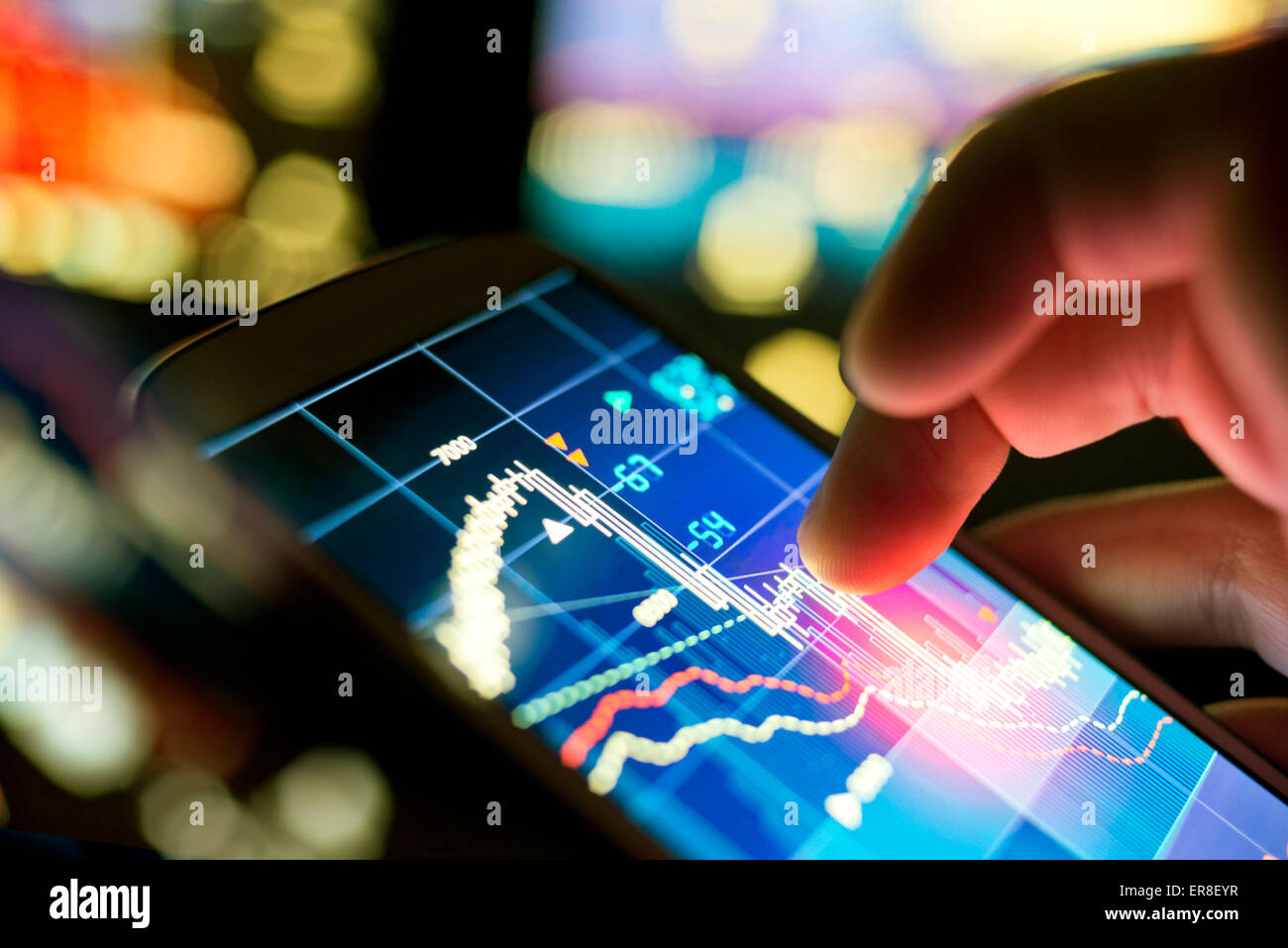 A businessman using a mobile phone to check stock market data. - Stock Image