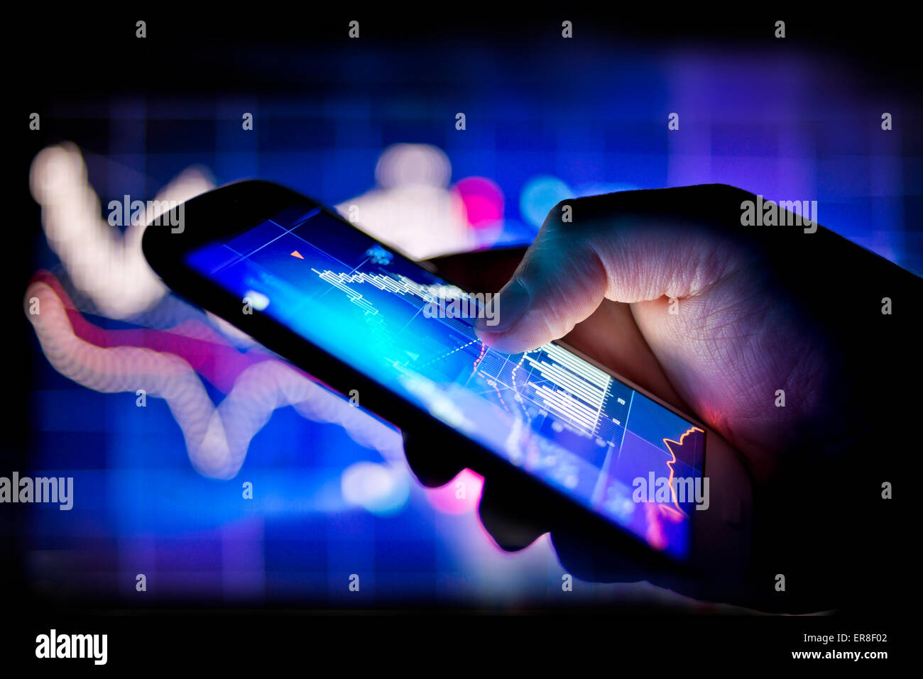 A person using a mobile phone to track real time stocks and shares data - Stock Image