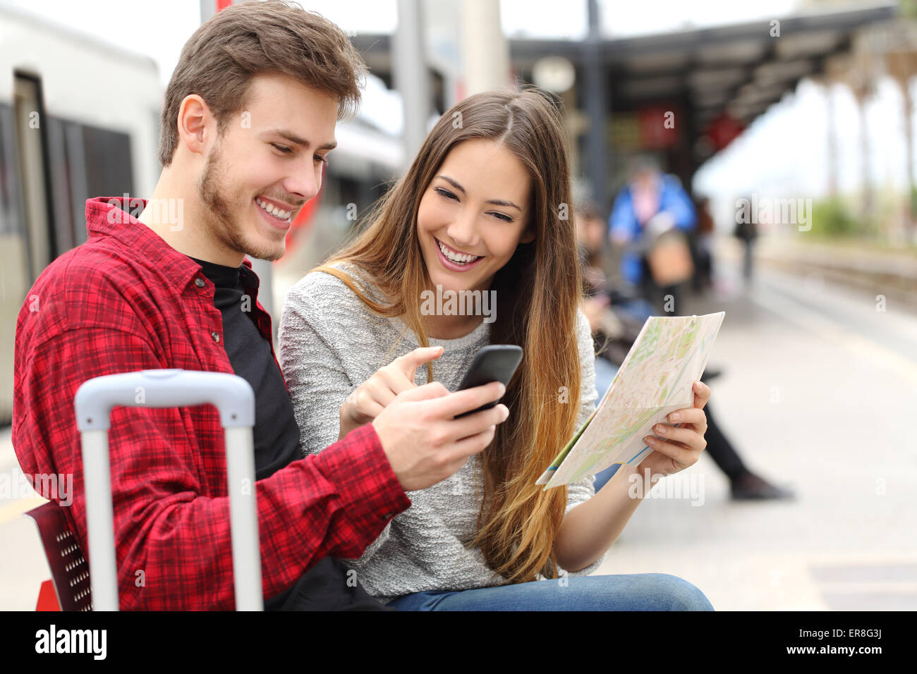 Tourists travelers consulting gps and guide from a smart phone in a train station - Stock Image