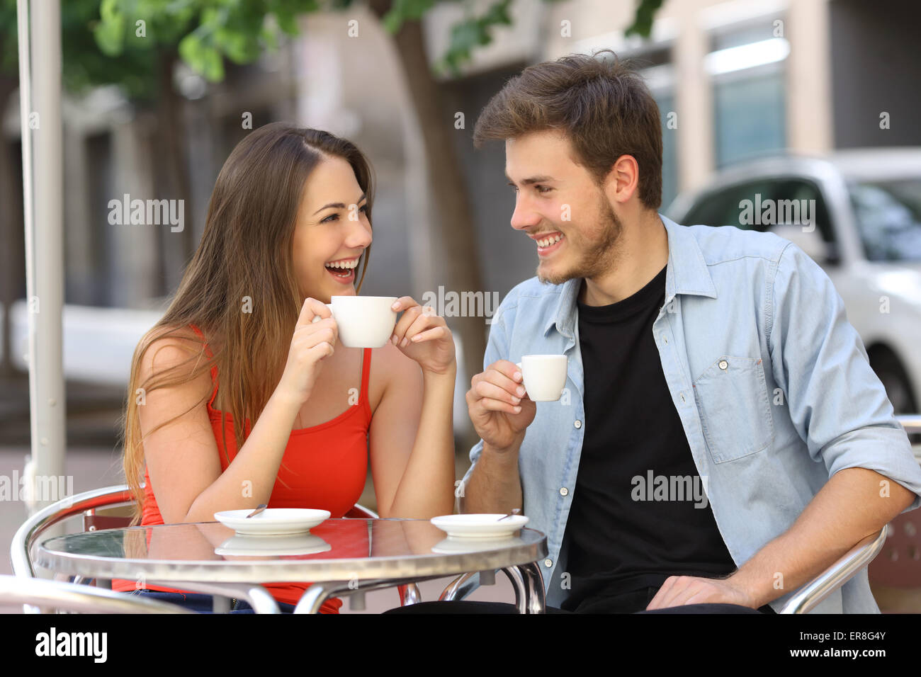 Happy couple or friends flirting talking and drinking in a restaurant terrace - Stock Image