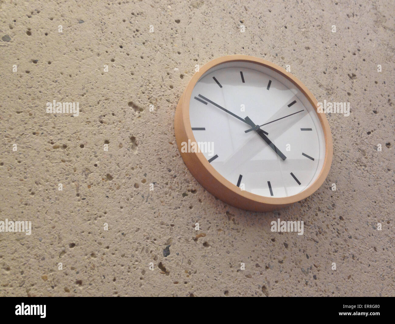 Simple classical analog wall clock on stone wall - Stock Image
