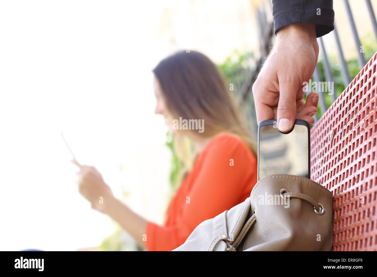 Thief stealing a mobile phone to a woman sitting on a bench in a park - Stock Image