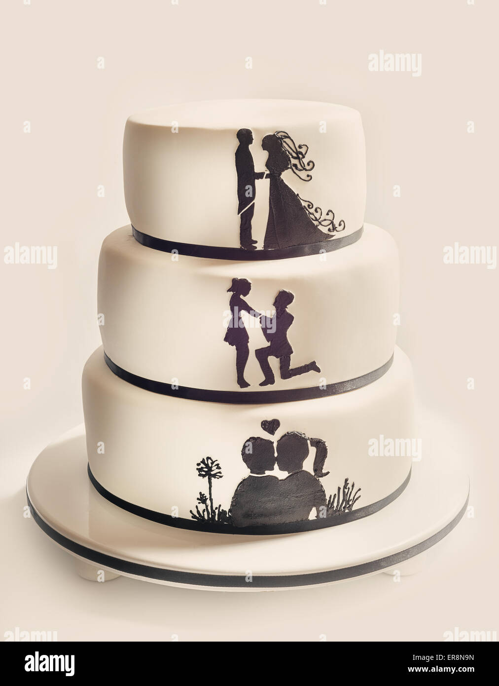 Details of a wedding cake, white sugar cream and black silhouettes. - Stock Image
