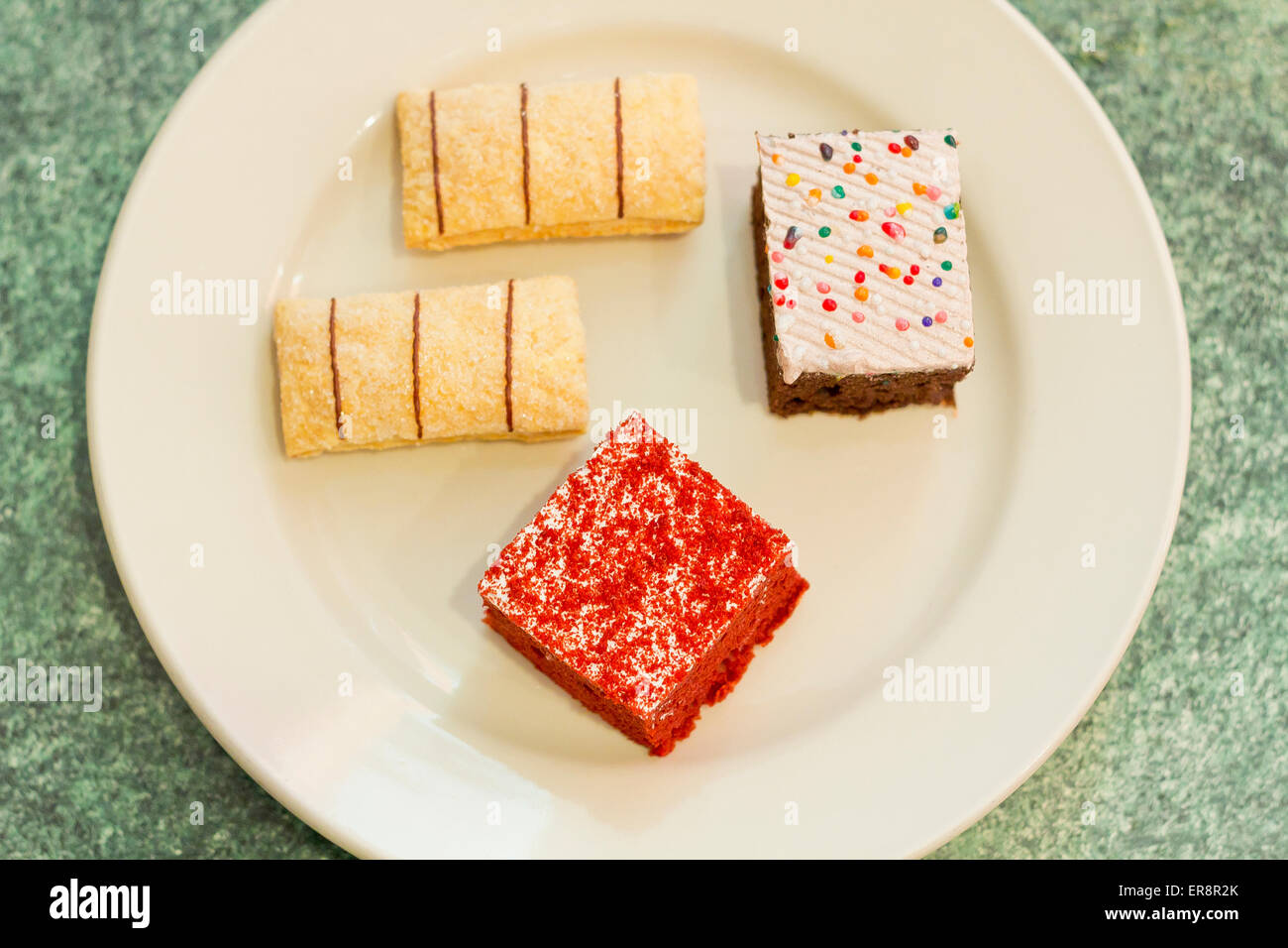 Assortment of sweet and colorful dessert cakes on a plate - Stock Image