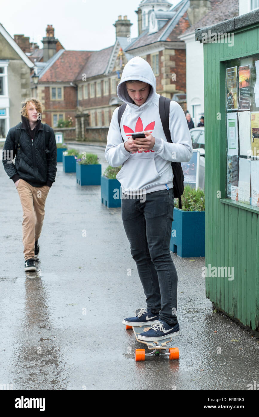 young lad using phone whilst on a skate board in Salisbury Wiltshire - Stock Image