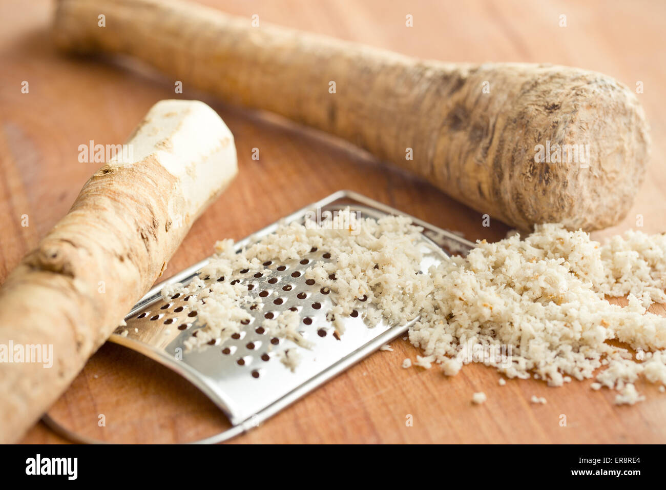 grated horseradish root on kitchen table - Stock Image