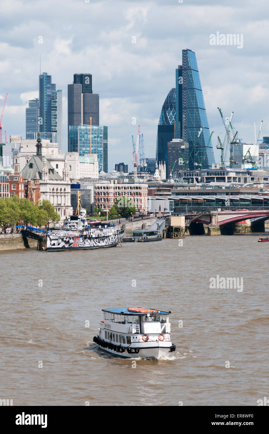 Office buildings on the London City skyline seen from Waterloo Bridge with a tourist pleasure cruise boat on the Stock Photo