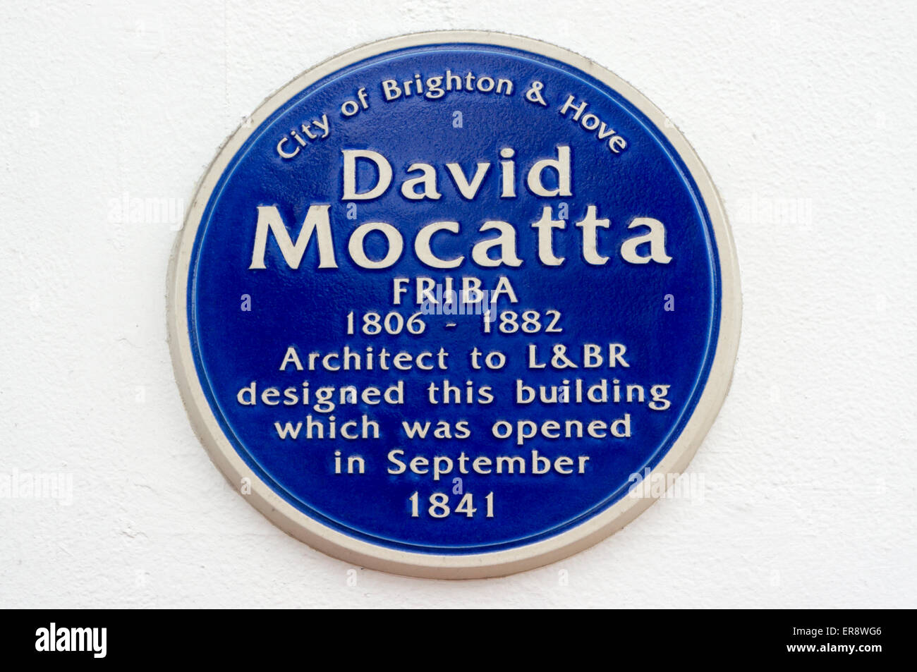 Blue plaque at Brighton station commemorates David Mocatta FRIBA, the Victorian architect who designed the building. - Stock Image