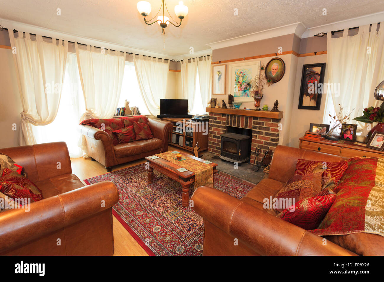 Lounge in english house with three leather sofas and wood burner - Stock Image
