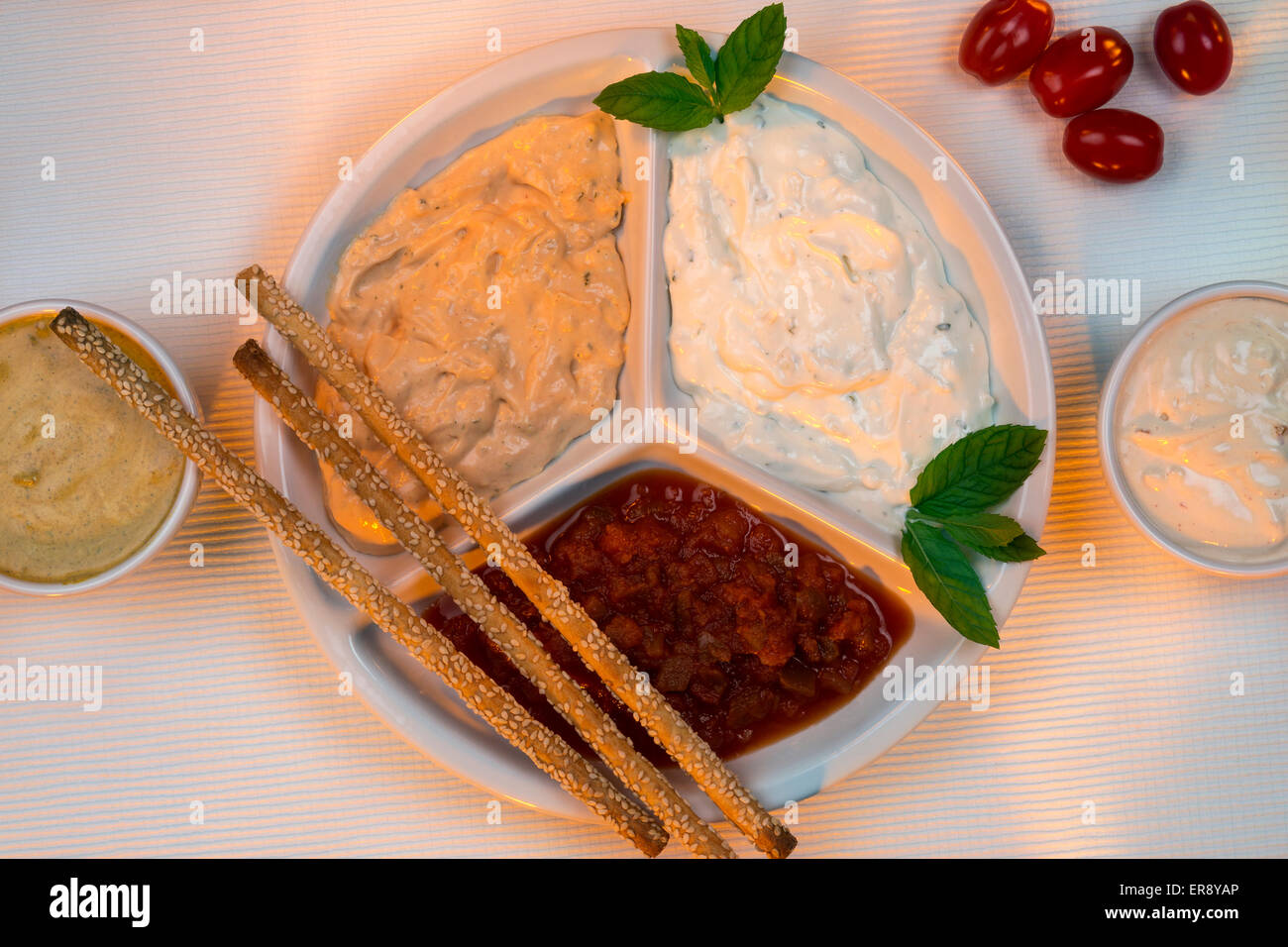 A selection of party dips with bread sticks and other crudites. - Stock Image