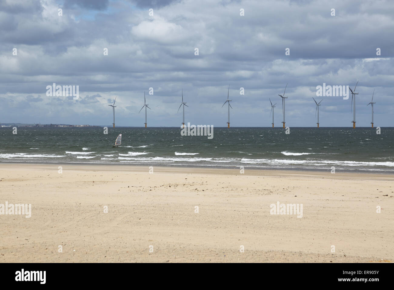 A windsurfer passes the Teeside wind farm photographed from Redcar beach. 27 offshore turbines in the estuary of Stock Photo