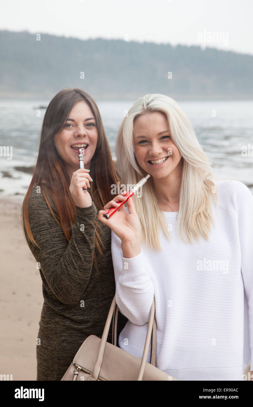 Two women in their 20's holding personal vaporizer's outside on a beach. - Stock Image