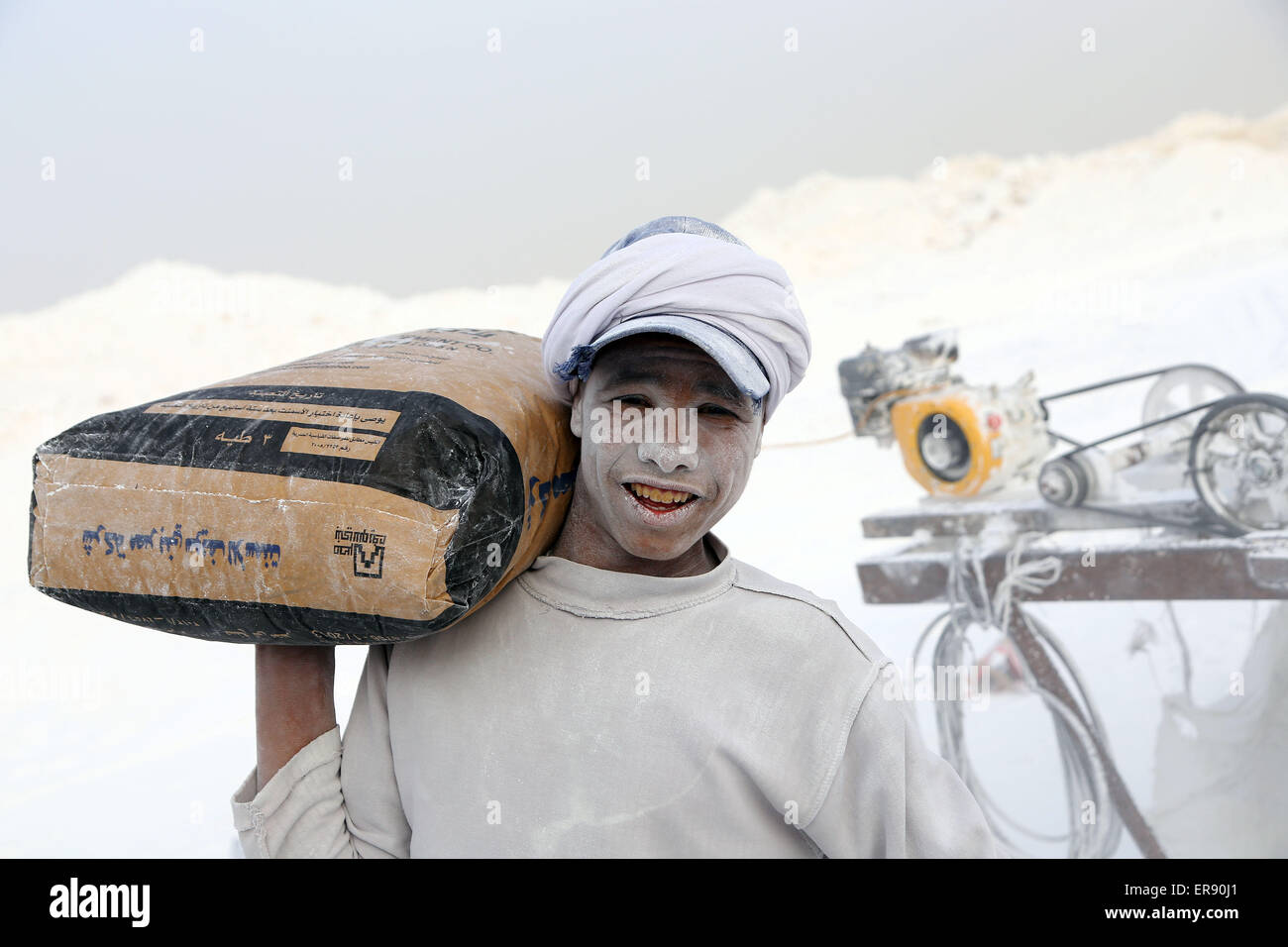Minya, Egypt. 28th May, 2015. An Egyptian worker carrying packed cement poses on a limestone quarry at the village - Stock Image