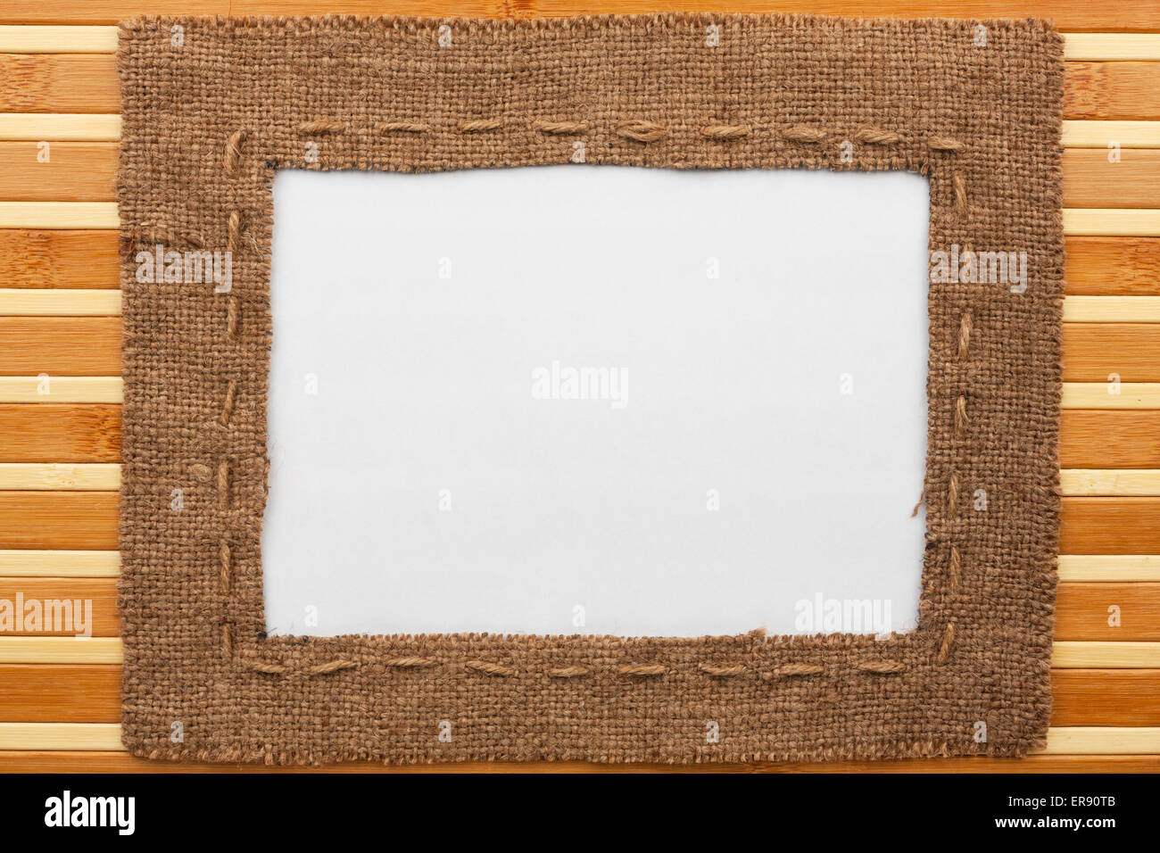 Frame made of burlap with white background lying on a bamboo mat ...
