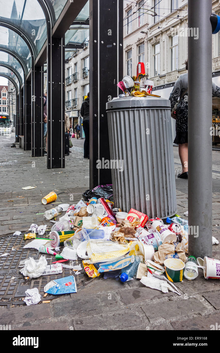 Overfull garbage can with piled up household refuse due to strike by waste processing firm at tramstop in city - Stock Image