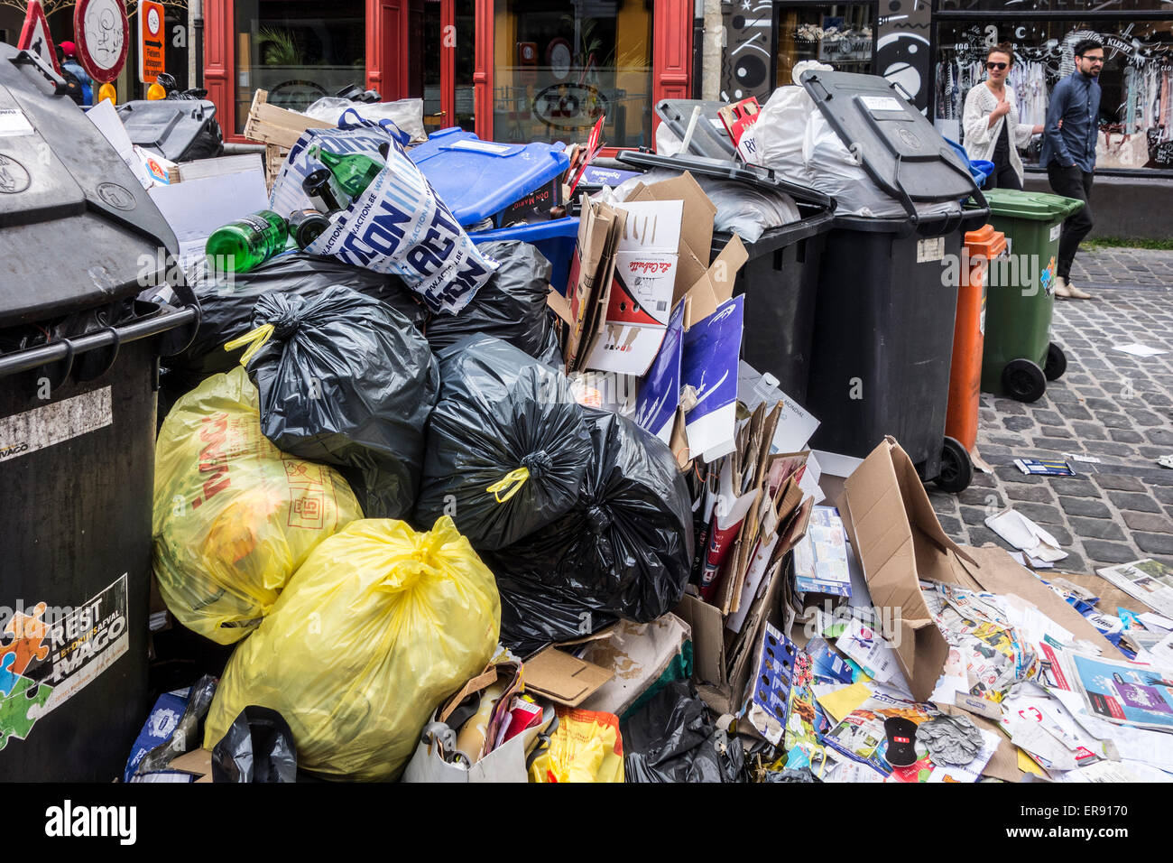 Pile of rubbish bags and garbage containers with household refuse blocking street in city due to strike by waste - Stock Image