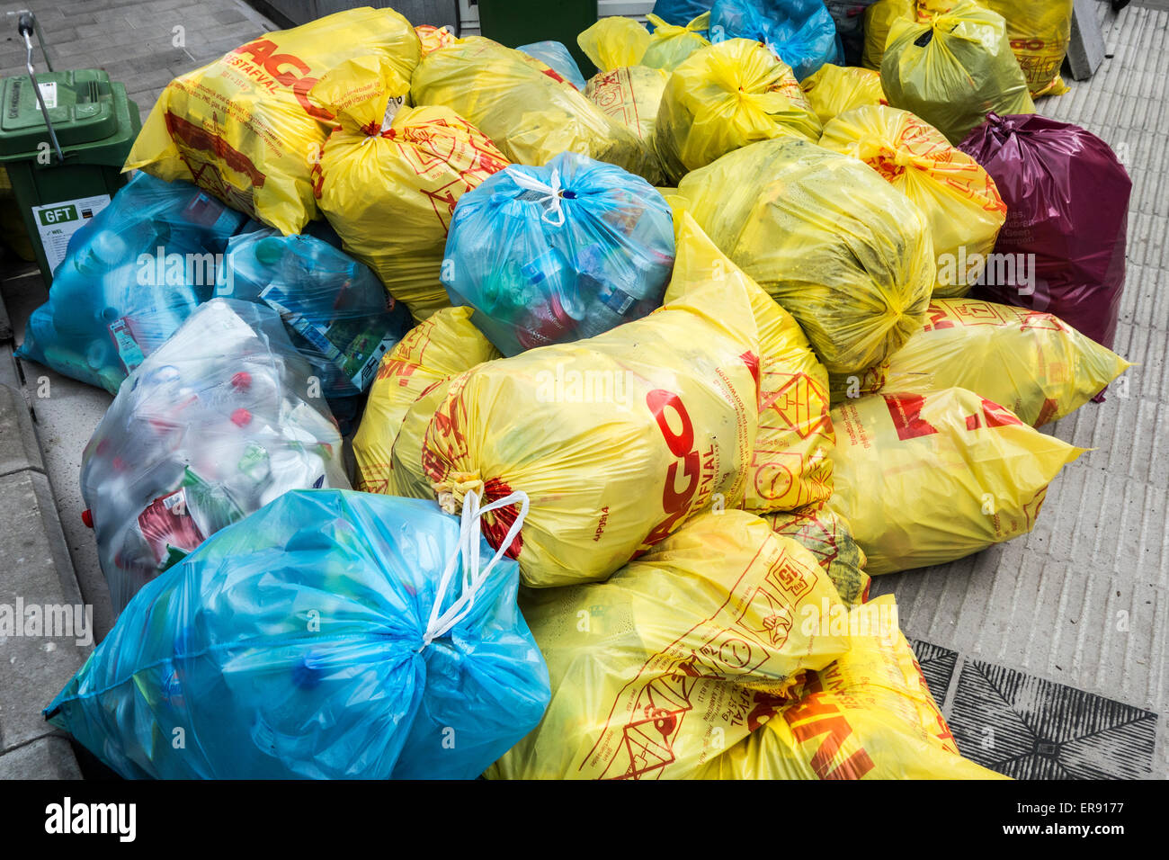 Piled up rubbish bags with household refuse blocking pavement due to strike by waste processing firm - Stock Image