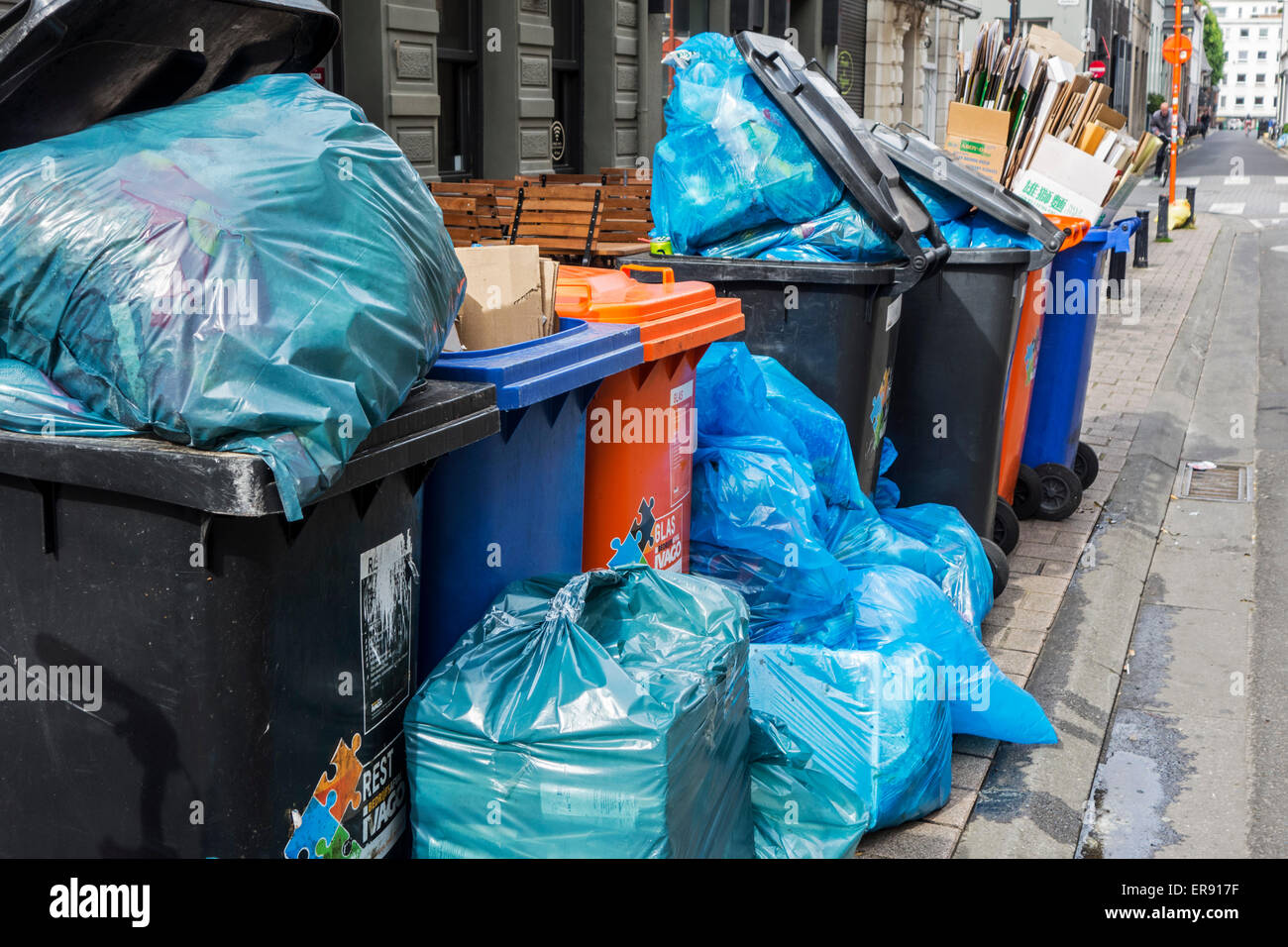 Rubbish bags and garbage containers with piled up household refuse blocking pavement due to strike by the waste - Stock Image