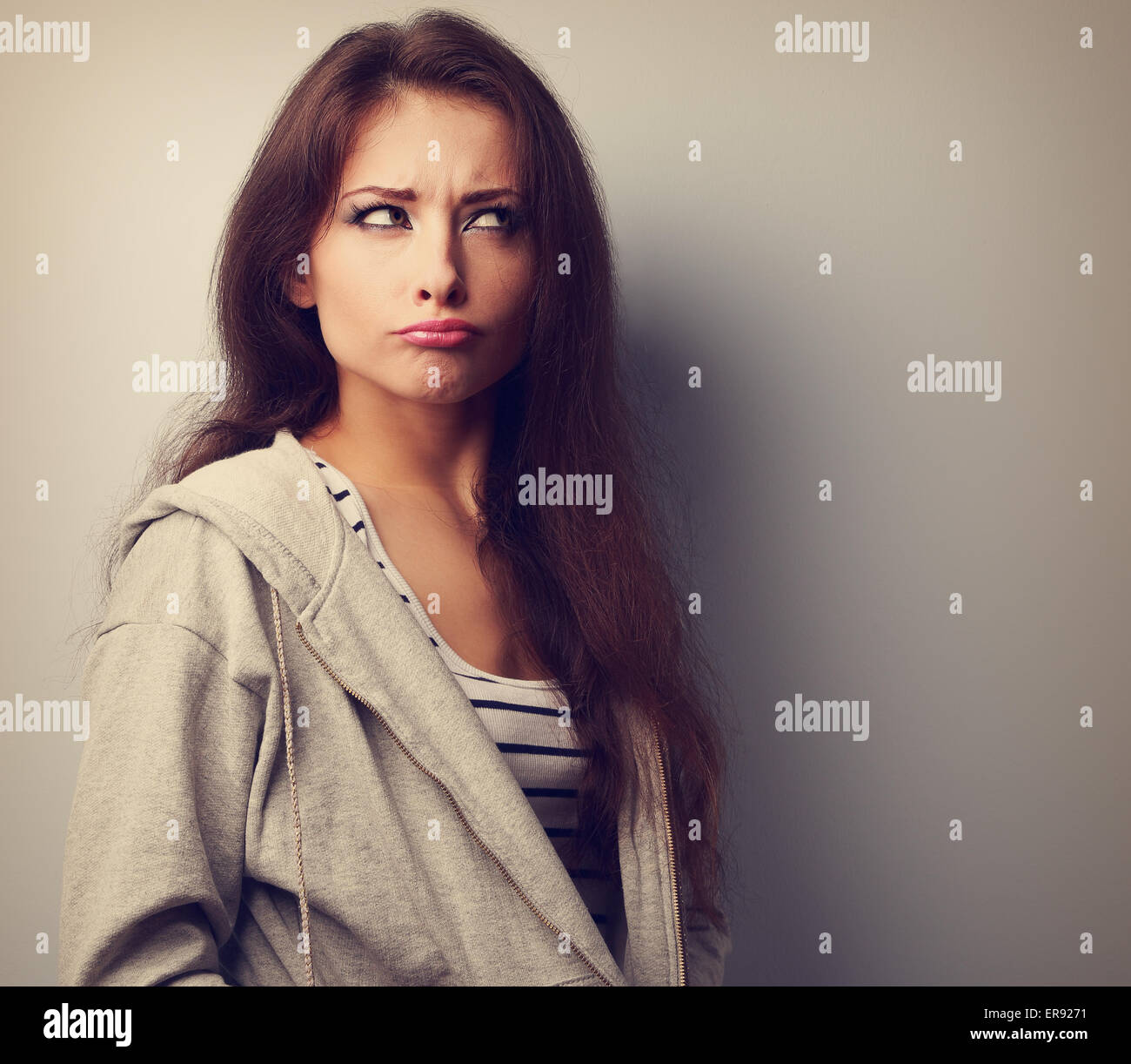 Grimacing fun young woman thinking and looking fun. Vintage portrait - Stock Image