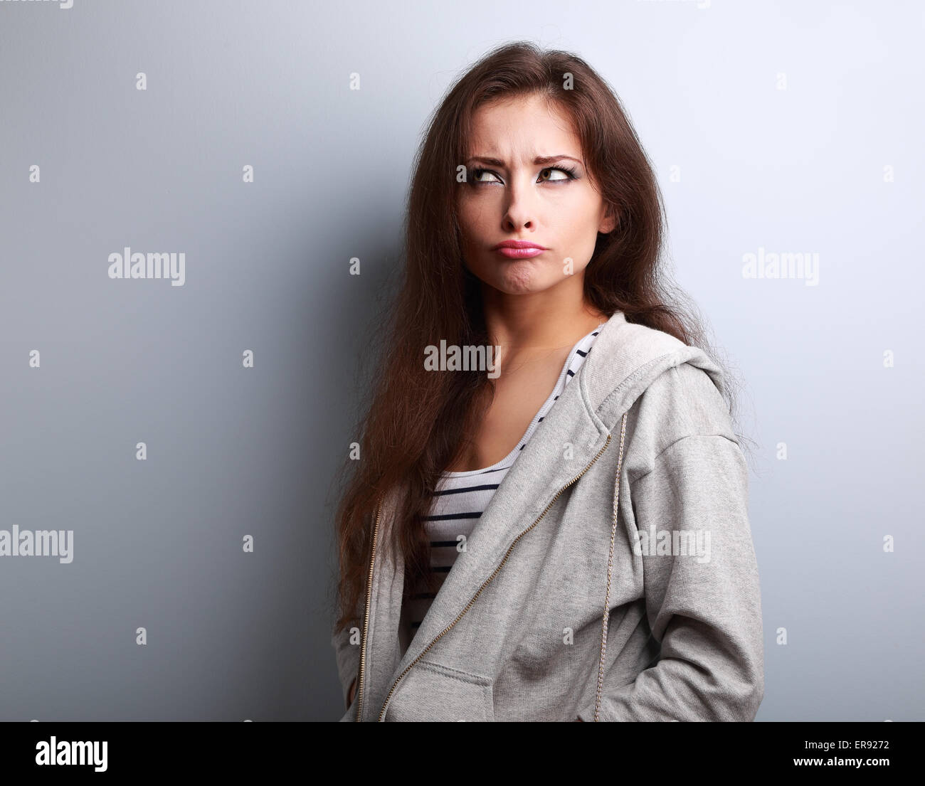 Grimacing fun young woman thinking and looking fun on blue background - Stock Image