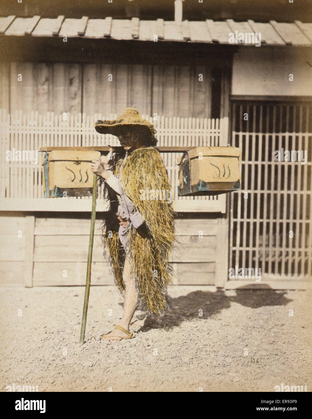Porter wearing protective outer garments made of straw. Photograph shows a porter, full-length, standing, facing - Stock Image