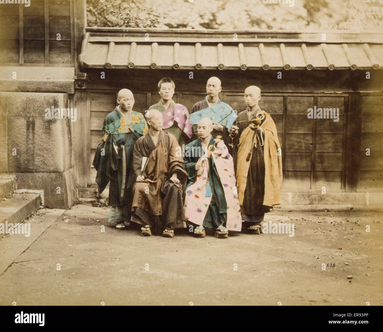 Six men, possibly monks, posed for group portrait, four standing and two sitting in front, five have their heads - Stock Image