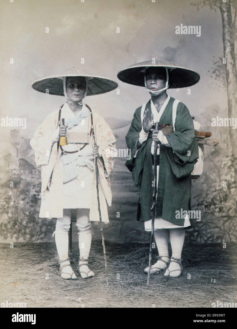 Two travelers with staffs, wearing hats, studio portrait. Photograph shows a studio portrait of two travelers, possibly - Stock Image