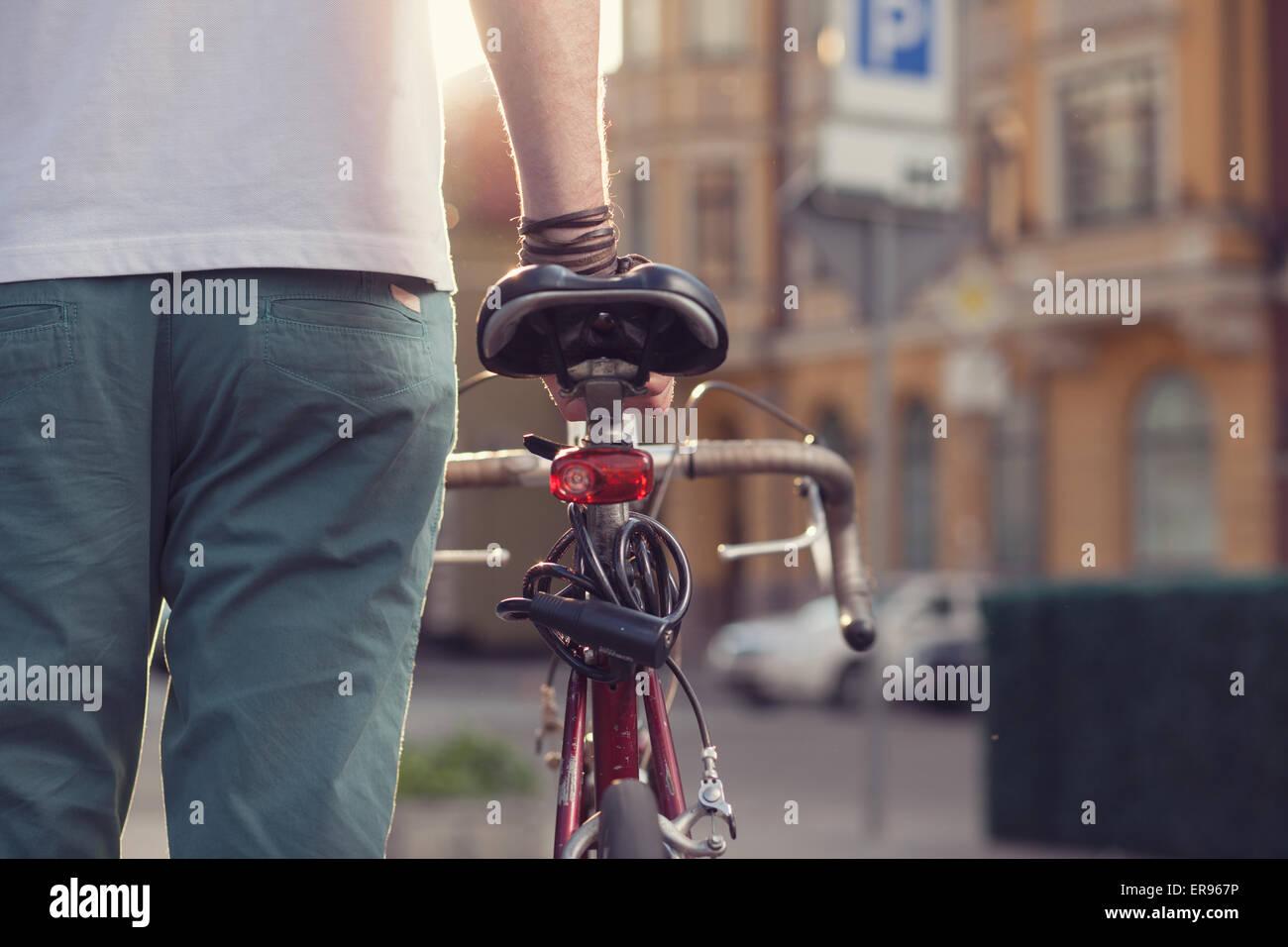 Closeup of stylish biker with vintage race bike - Stock Image