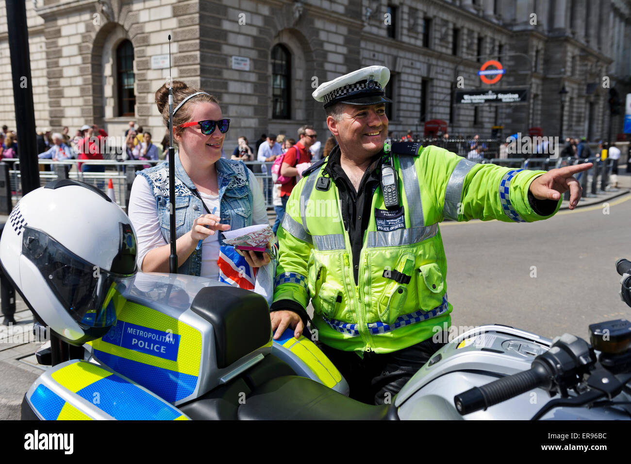 A male traffic police officer in bright yellow jacket with high powered motorbike talking to one young woman, London, - Stock Image