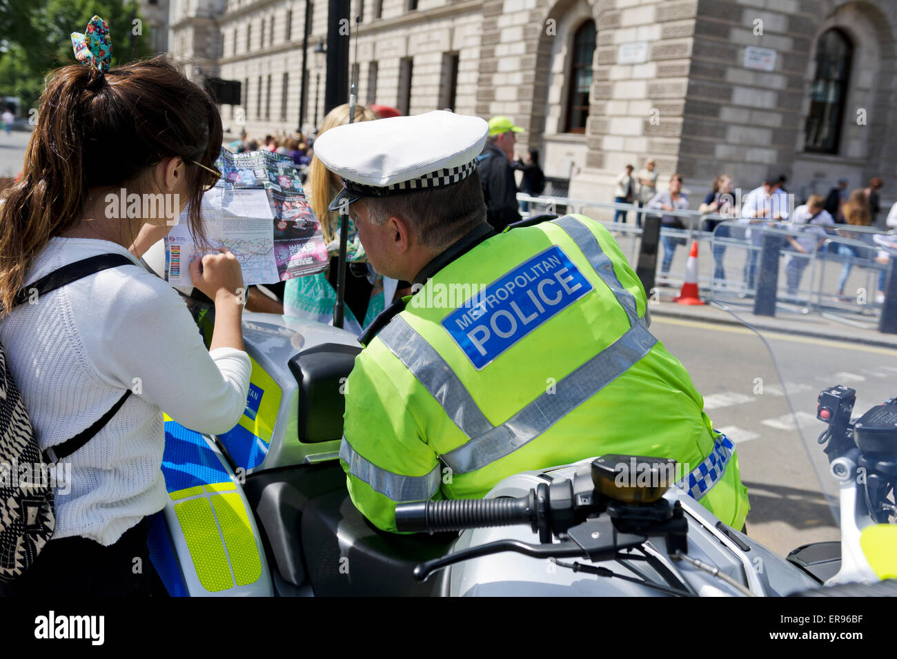 A male traffic police officer in bright yellow jacket with high powered motorbike talking to three young women, - Stock Image