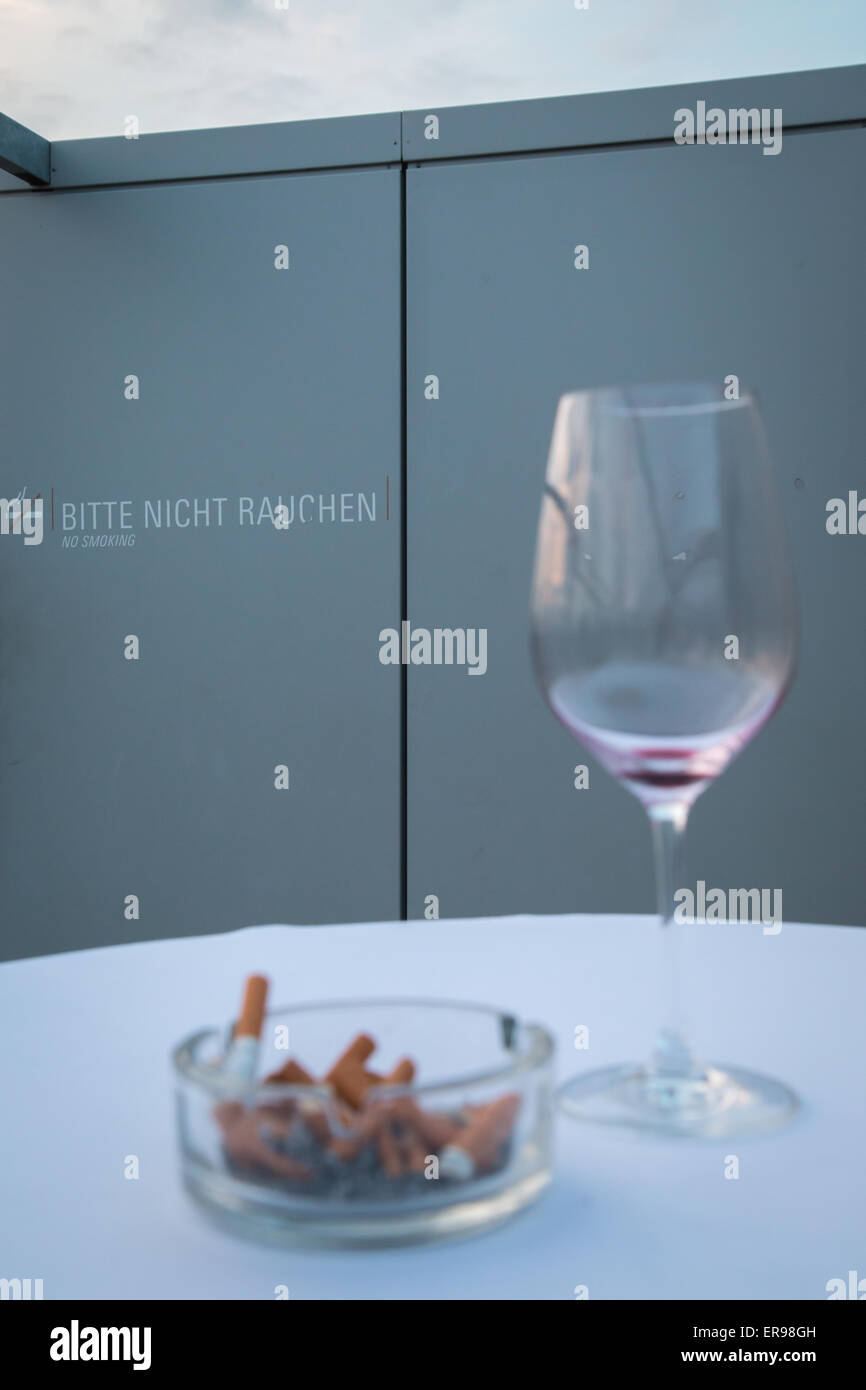 A full ashtray and an empty glass of wine in front of sign forbidding smoking Stock Photo