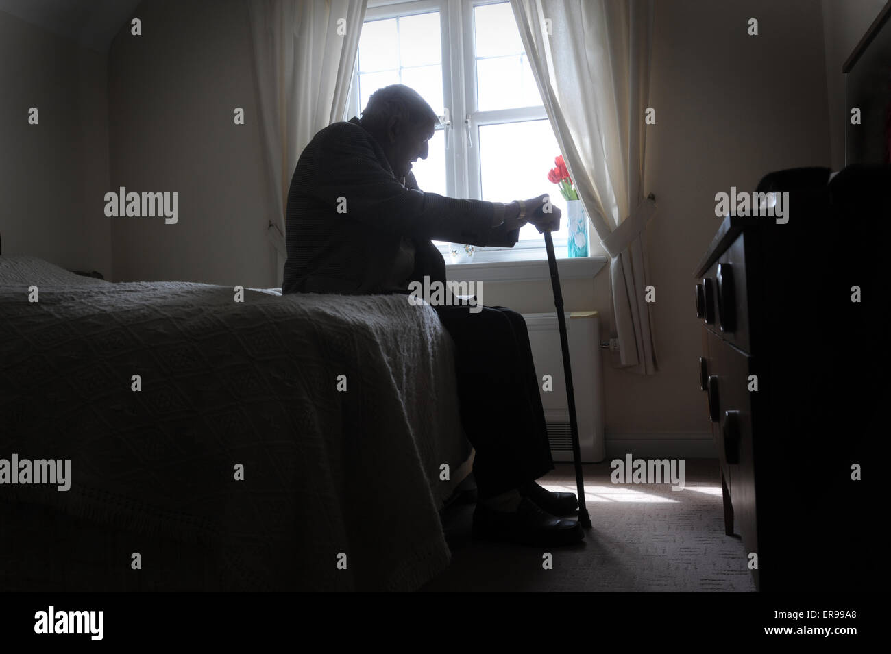 Silhouetted old age pensioner re loneliness lonely oap retirement depression man men depressed alone elderly care home uk cry