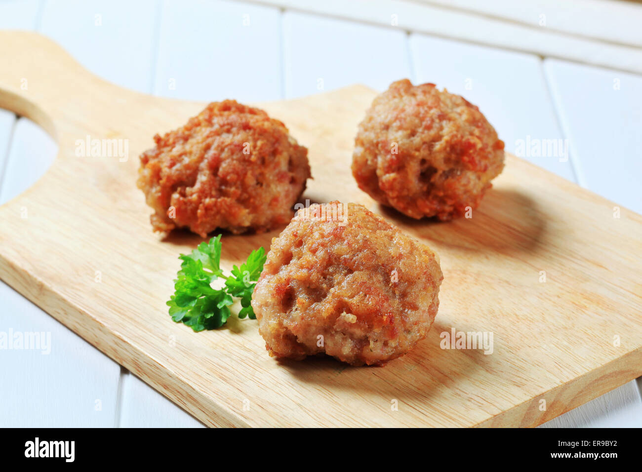 Meat balls on wooden cutting board - Stock Image