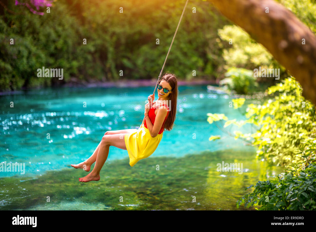 Woman swinging on the river - Stock Image