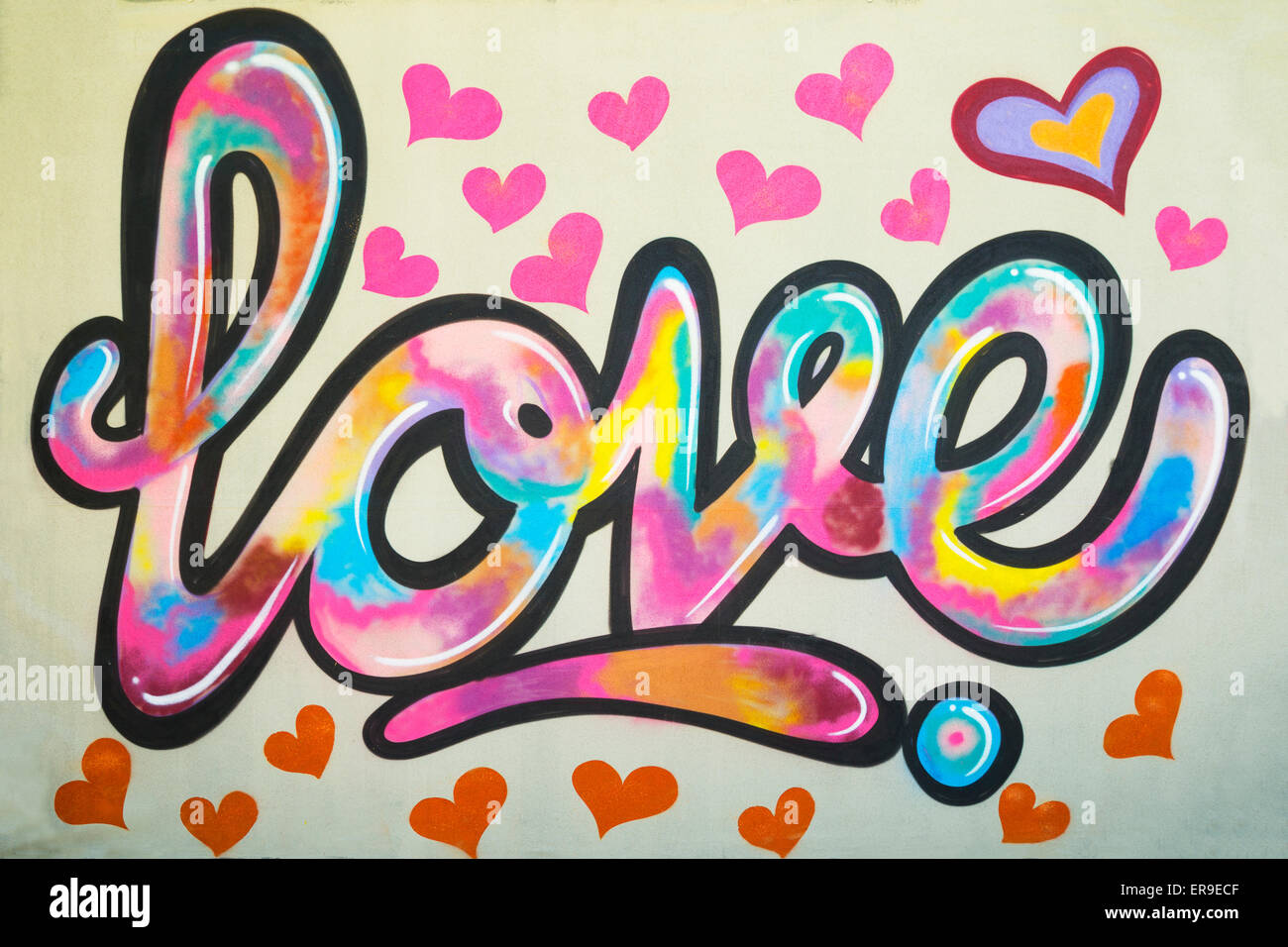 Graffiti text Love on the wall with many pink colored heart shapes around close up view